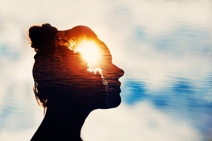 Silhouette of young woman on sky background with sun in her head.